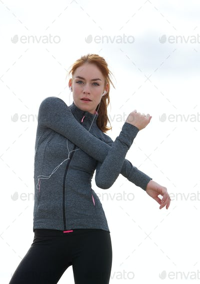 Sporty young woman stretching muscles