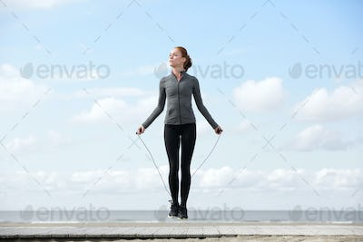 Sporty woman warming up with jump rope