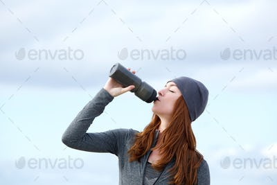 Fitness woman drinking water from bottle outdoors