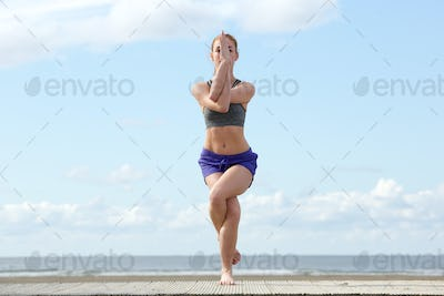 Young woman balancing in yoga position