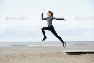 Young female runner jumping outdoors