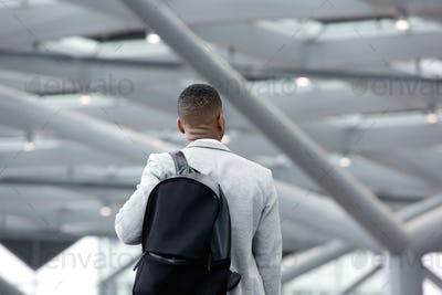 Black man standing in airport with bag