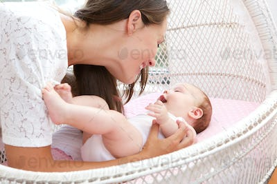 Young woman smiling with newborn infant