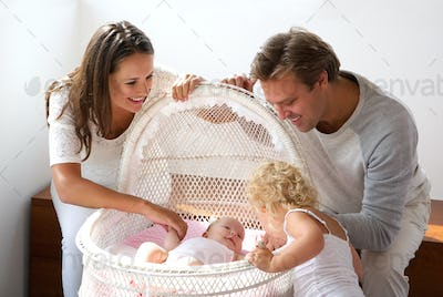 Young family smiling at newborn in cot