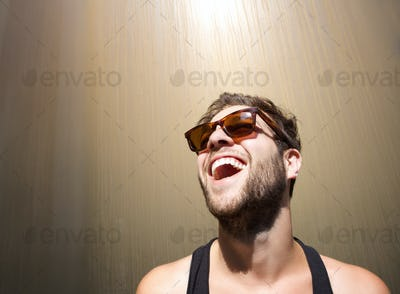 Cheerful young man laughing with sunglasses