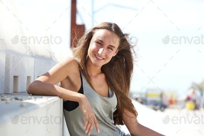 Happy young woman sitting outside