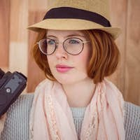 Hipster smiling and holding camera on wooden background