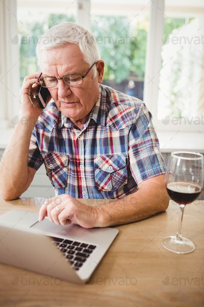 Worried senior man taking on phone while using laptop at home