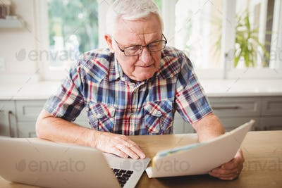 Worried senior man looking at a document while using laptop