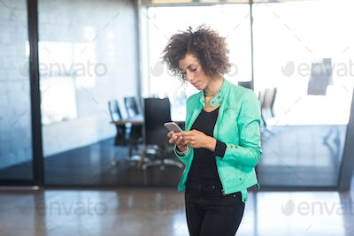 Young woman using mobile phone in front of conference room in the office