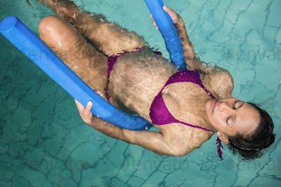 Pregnant woman with foam roller in the pool