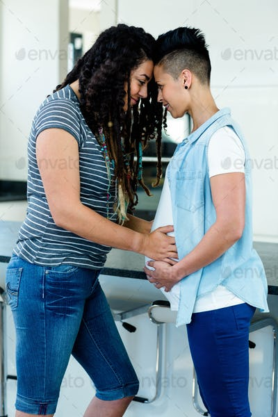 pregnant lesbian couple standing face to face and embracing in kitchen