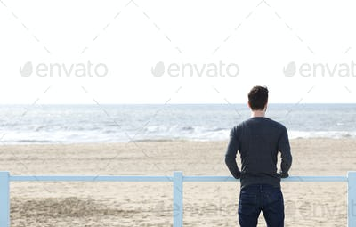 Man standing alone looking at sea
