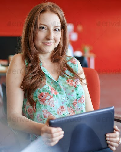 Confident female designer working on a digital tablet in red creative office space