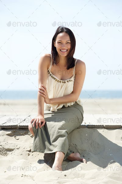 Cheerful young woman sitting at the beach