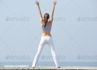 Woman with arms raised at the beach