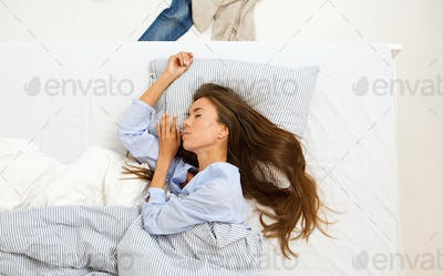 Young woman sleeping in comfortable bed