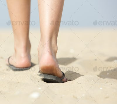 Woman walking in slippers on sand