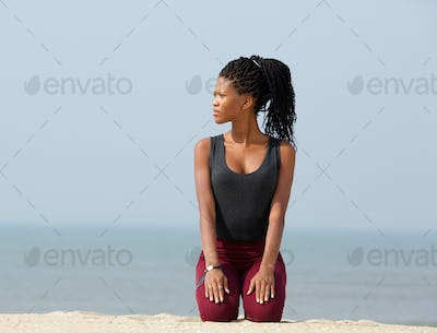 Young african woman kneeling outdoors on beach
