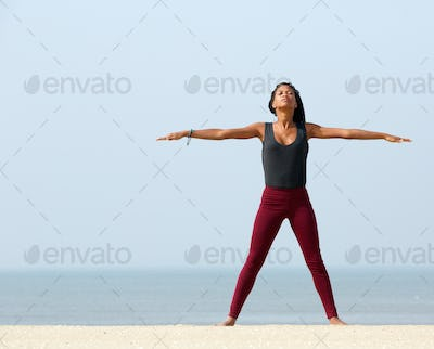 Woman yoga stretching at the beach