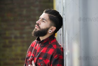 Man with beard standing outdoors alone