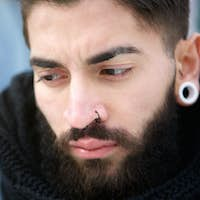 Attractive young man with beard and piercings