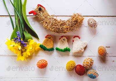 Crocheted Easter eggs, chickens and daffodils, wooden background