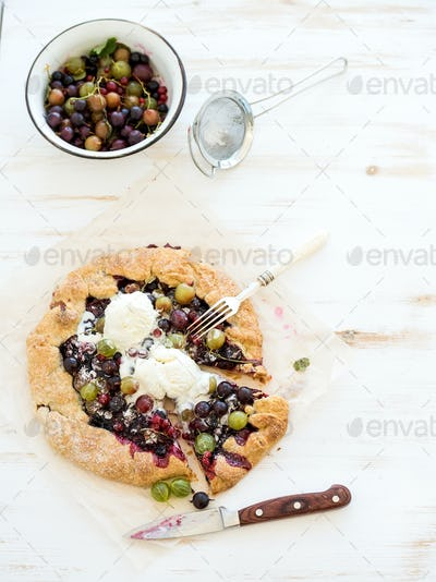 Summer crostata or galette pie with fresh garden berries and vanilla ice-cream