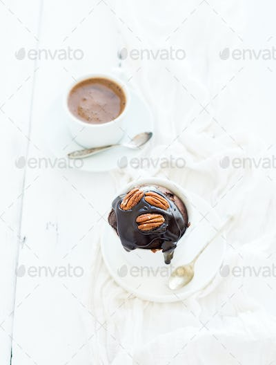 Tasty homemade brown muffin with chocolate ganache icing, pecan nuts and coffee