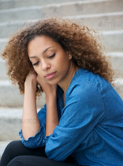 Portrait of a elegant young woman sitting alone outdoors