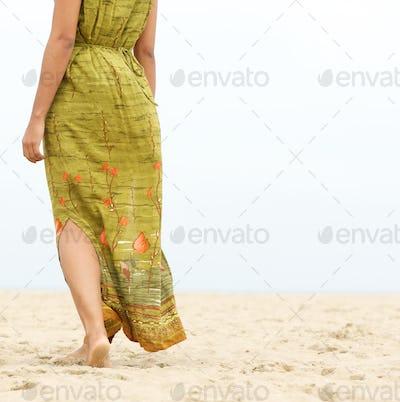 Barefoot woman walking forward at the beach