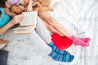 Beautiful legs of two women sitting and reading a book