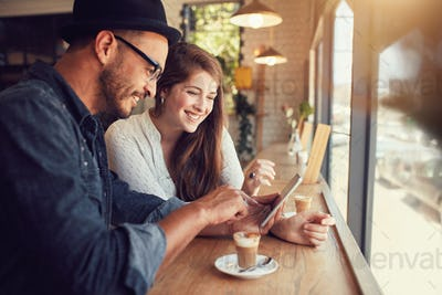 Happy couple in a coffee shop using digital tablet