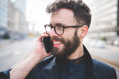 Portrait of young handsome caucasian bearded man talking smartph