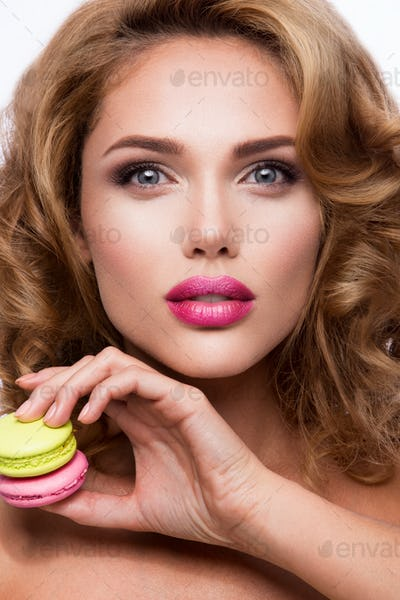Close-up portrait of beautiful woman with bright make-up. Macarons.