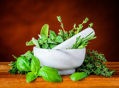 Pestle and Morthar with Green Basil, Mint and Rosemary