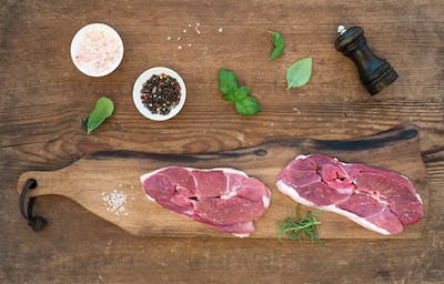 Raw fresh meat lamb entrecote and seasonings on cutting board over rustic wooden background.