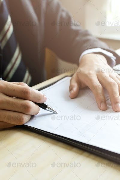 Human Hand Signing on Formal Paper at the workplace