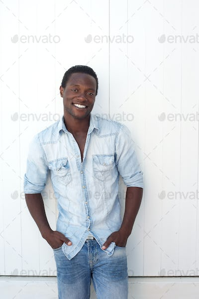 Casual african american man smiling outdoors against white background