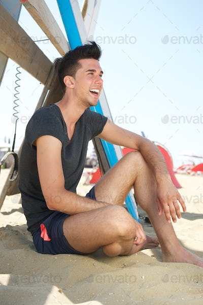 Happy young man sitting at the beach