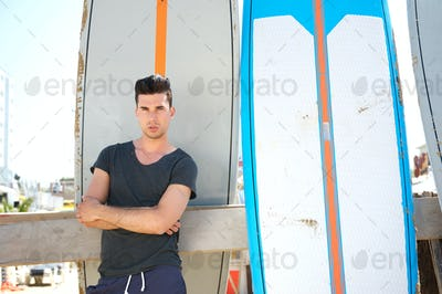Handsome young man standing with surfboards outdoors