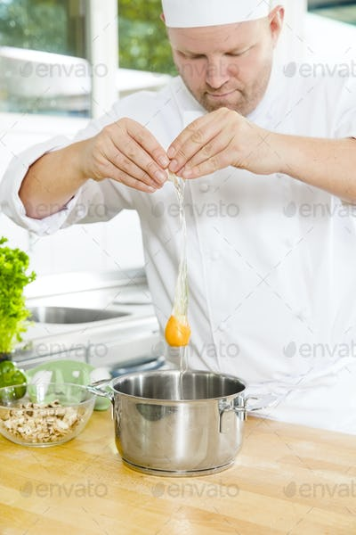 Chef cracking egg in large kitchen