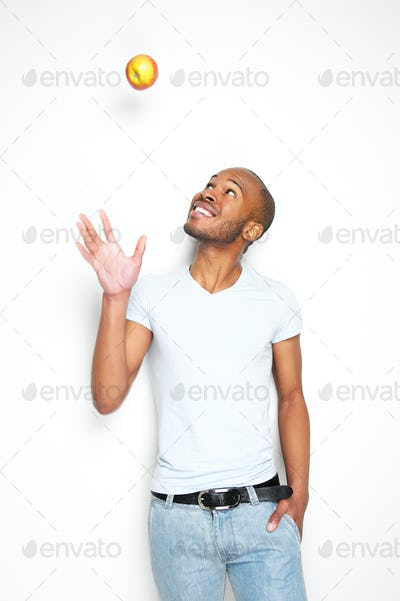Smiling african american man throwing an apple in the air