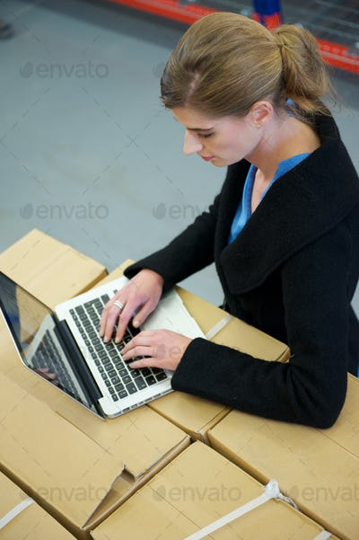 Business woman typing on laptop in warehouse