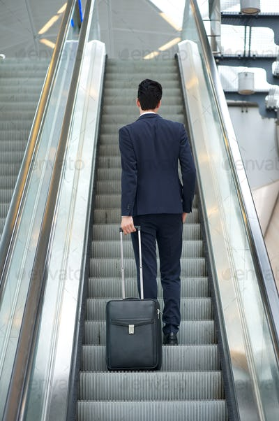 Business man going up escalator with bag