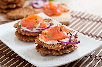 Buckwheat pancakes with salted salmon and sour cream close up