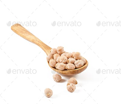 Uncooked chickpeas in wooden spoon on white background