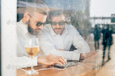 Two young bearded caucasian modern business man sitting in a bar