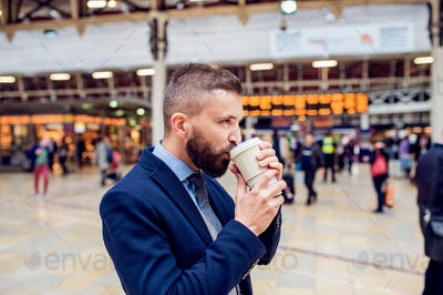 Hipster businessman drinking coffee at the train station