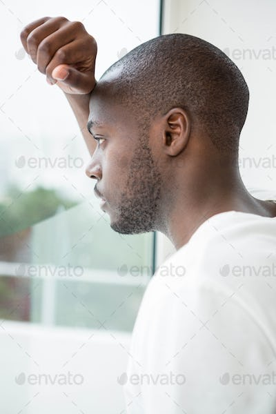 Thoughtful man looking out of window in morning
